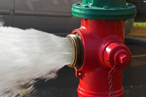 Red fire hydrant with water pouring out