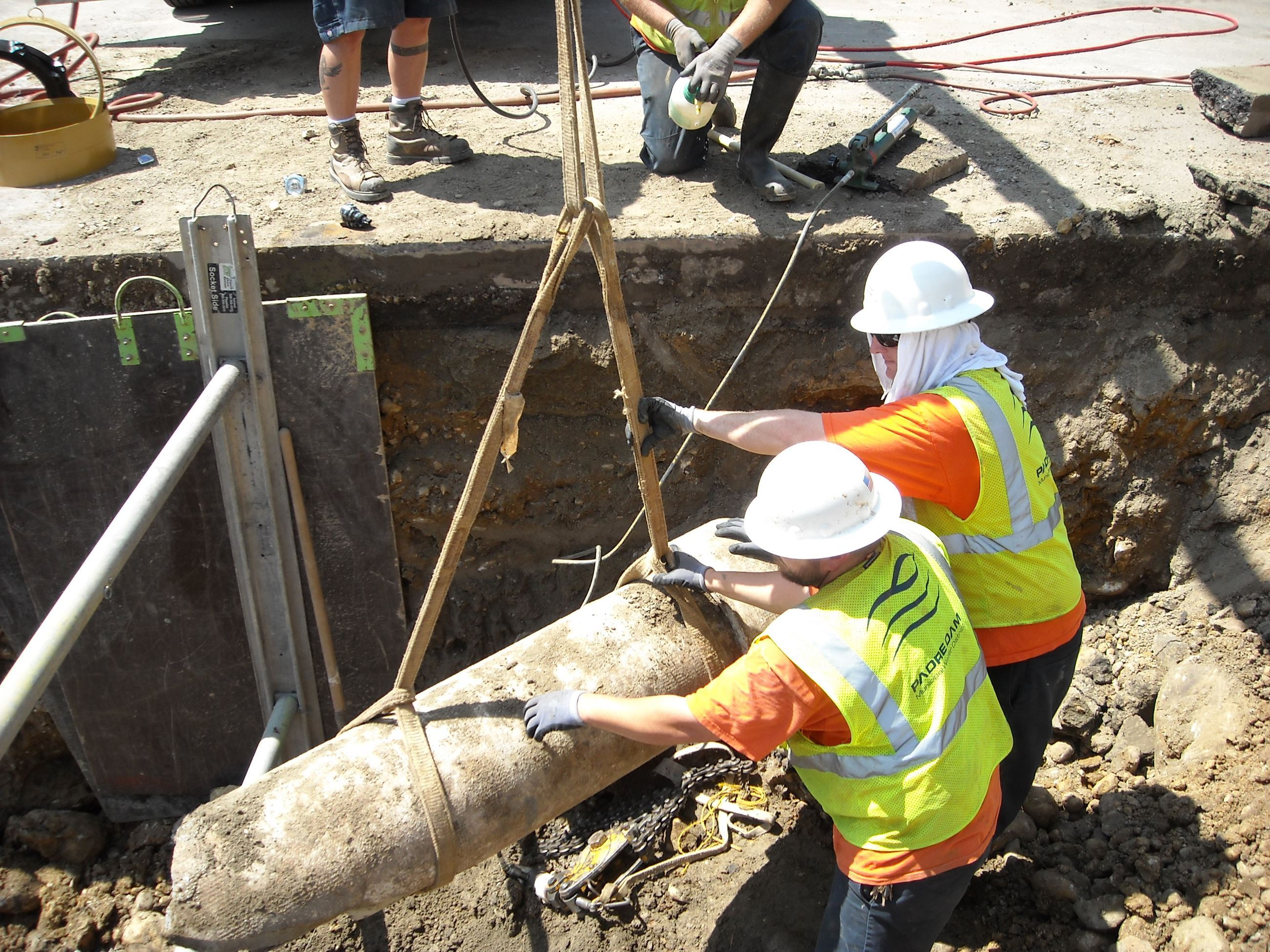 two men helping to install sewer lines