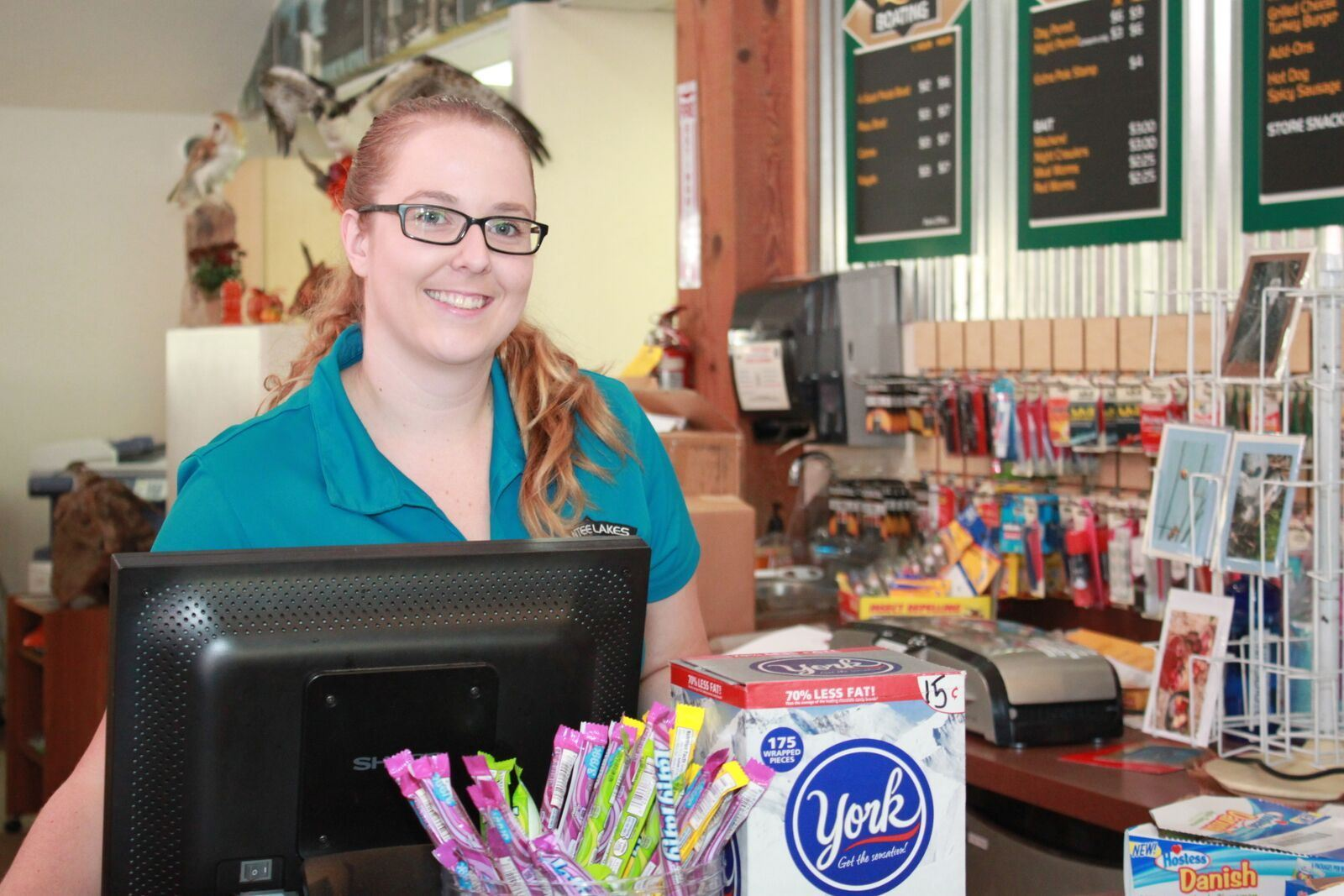 Woman standing behind cash register smiling