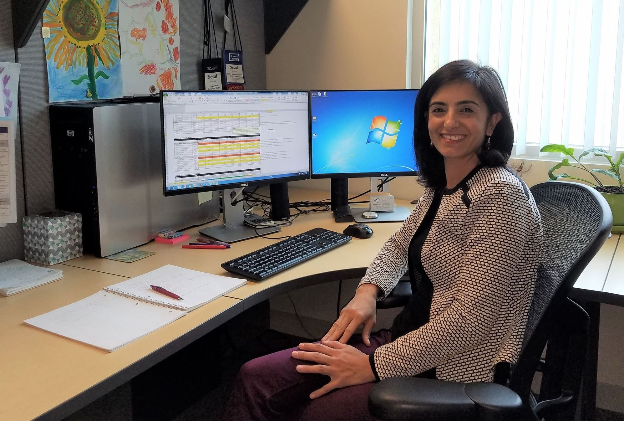 Woman sitting at computer smiling for camera
