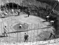 Black and white image of worker on a dam