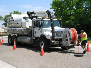 Vactor Truck on a road with man using wiring